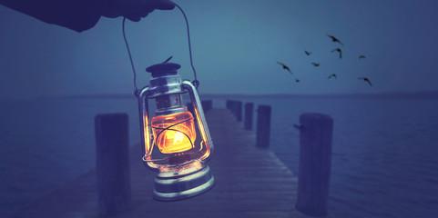 Fotomurales - alte Öllampe leuchtet den Weg am Bootssteg