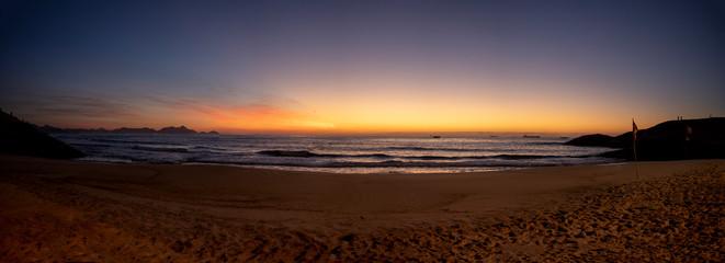 Super wide panorama of crack of dawn just before sunrise at the Arpoador Devil's beach in Rio de Janeiro, Brazil