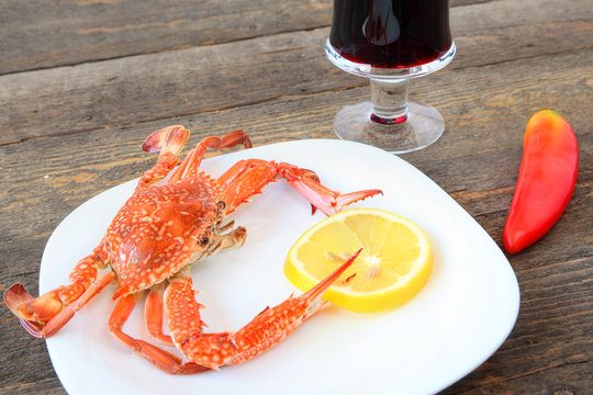 Red boiled crab, sliced fresh lemon, hot red paper and ice cubs on a white plate. Glass of red wine. Seafood. Still life on old wood surface