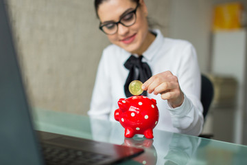 Young smart businesswoman collecting bictoins into piggy bank