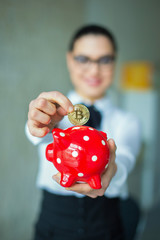Young smart businesswoman collecting bictoins into piggy bank selective focus