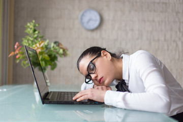 Tired woman sleeping on desk at laptop