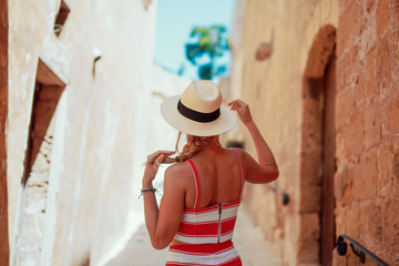 Young traveler woman in hat on Mediterranean street back view