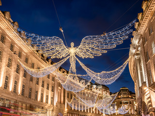 Big angel shape decorations outdoors on Regent Street illuminated by Christmas lights in winter holiday season in London, UK