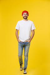 young hipster man wearing hat , suspenders, isolate on yellow background.