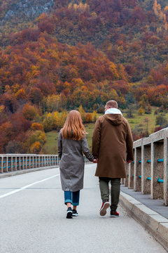 Сouple walks along the Durdevica Tara Bridge, Montenegro. The guy and the girl hold hands.