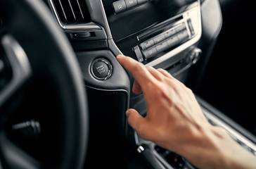 Man driver pushing a start ignition button switch in the modern luxury car.