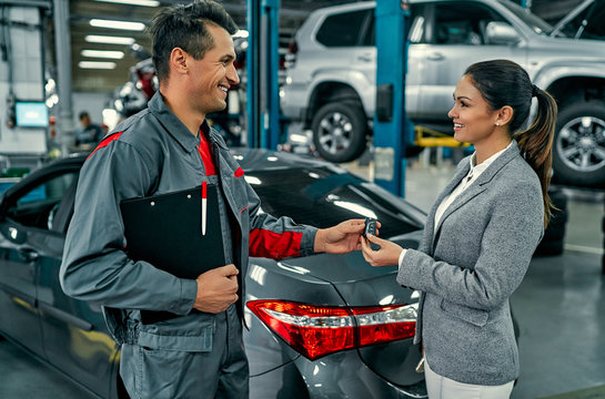 Beautiful businesswoman and auto service mechanic are discussing the work and giving keys. Car repair and maintenance.