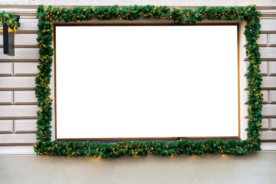 Blank showcase windows sign board decorated with green Christmas tree branches, garland lights of store in european city street