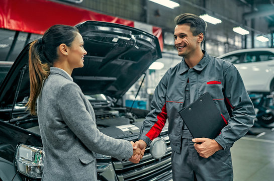 Beautiful businesswoman and auto service mechanic shaking hands. Car repair and maintenance.