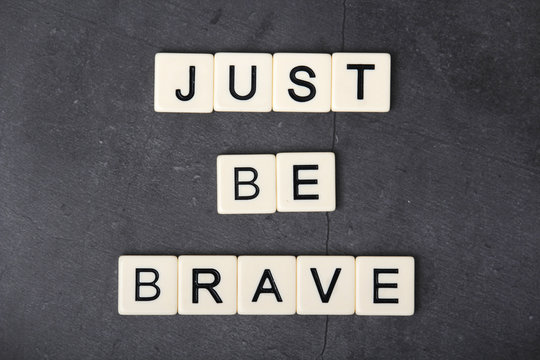 A motivational quote Just be brave formed with tile letters