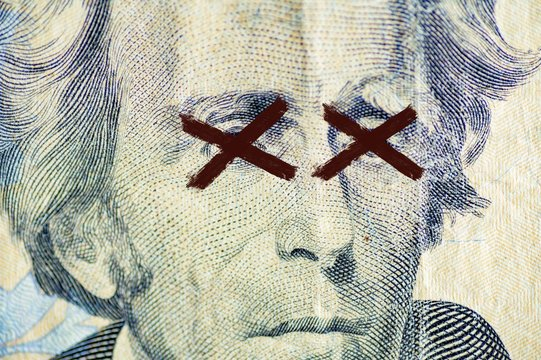 Closeup shot of the Andrew Jackson, on the dollar bill with x painted over its eyes
