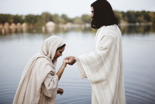 Shallow focus shot of a female wearing a biblical gown while holding the hand of Jesus Christ