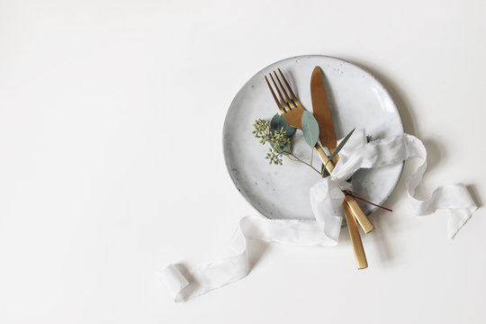 Festive table setting. Golden cutlery, berry eucalyptus branch, porcelain plate and silk ribbon isolated on white table background. Mediterranean wedding or restaurant menu concept. Flat lay, top view