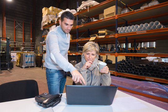 woman manager in warehouse talking to worker