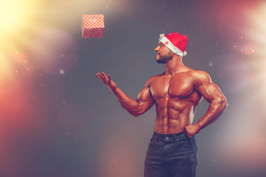 Handsome Shirtless Santa Claus Trowing Present Box in the Air