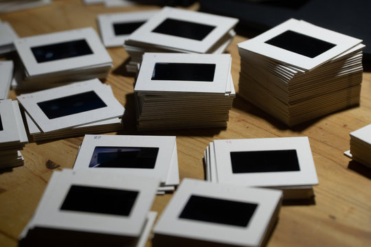 piles of 35mm slides on a wooden table
