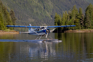 Seaplane landing in a remote cove near Ketchikan, Alaska. Calm water and beautiful tree lined mountains in the background
