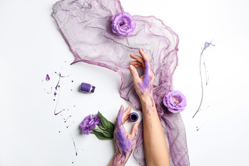 Artist's hands in paint, flowers and cloth on white background