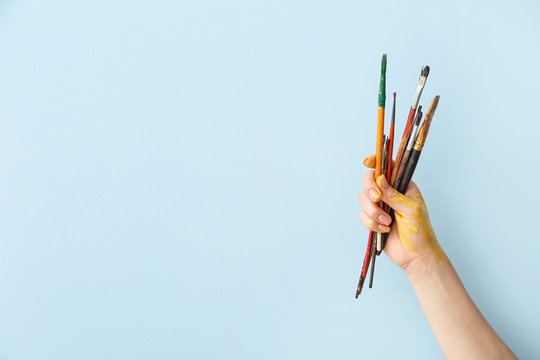 Hand of artist with brushes on color background