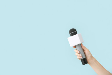 Journalist's hand with microphone on color background