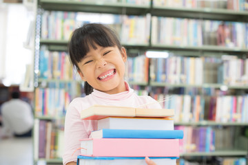 child girl holding a stack of books in the library