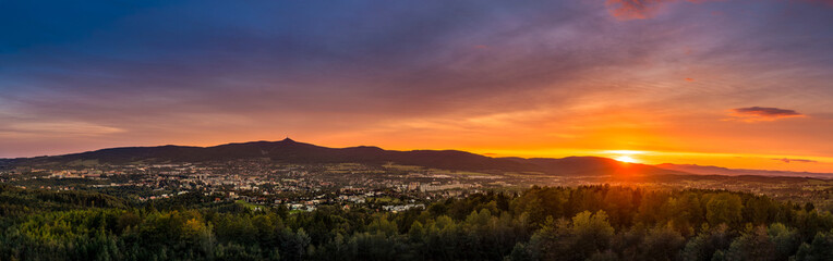 Spoed Foto op Canvas Chocoladebruin Dramatic Liberec sunset sky with illuminated clouds in the mountains. Dark black silhouette of mountain ridge and Jested transmitter tower at the bottom.