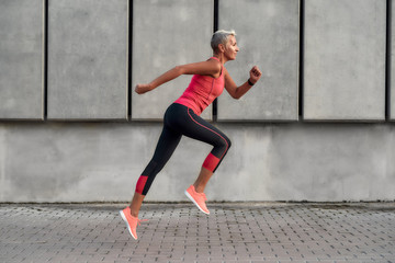 Full of energy. Side view of active middle aged woman in sport clothing jumping while exercising outdoors