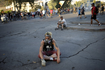 A protester sits on the ground during a protest against Chile's government in Santiago