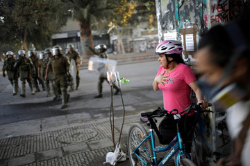 A woman gestures as members of the security forces disperse a protest against Chile's government in Santiago