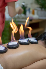 spa concept of orchid flower, zen basalt stones with drops, lilac candles, beads
