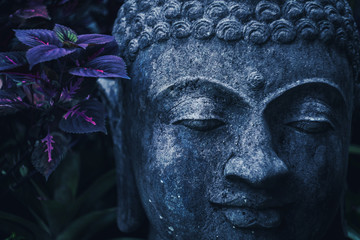 Stone Buddha face close-up in trend blue color toning. Handmade carved Buddha statue in balinese garden as decoration.