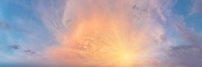Sunset cloudy sky with the orange sun