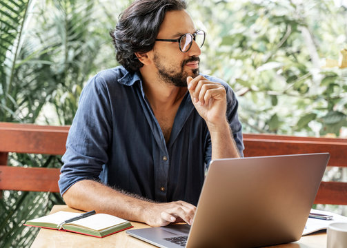 Handsome young curly latin man with glasses working on a laptop on the terrace of his house. Creative remote work, programmer, copywriter, writer