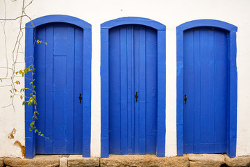 Facade with three typical blue wooden doors in Unesco World Heritage town Paraty, Brazil