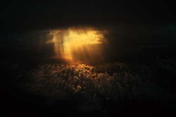 Dramatic god light rays shining from dark cloud on to clouds expanse on the sky. power of hope and god induce strength. light through darkness.