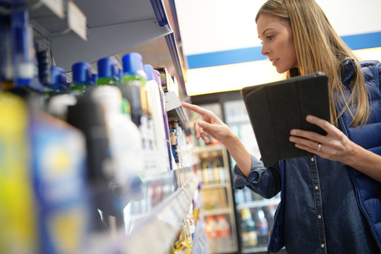 Store manager controlling stocks on shelves