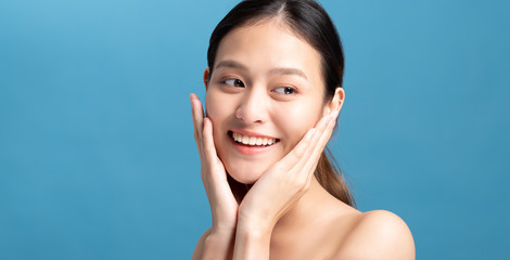 Portrait of confident beautiful asian woman with hand beside face and smiling isolated on blue color background with studio shot.Skincare for healthy face concept. Fotomurales