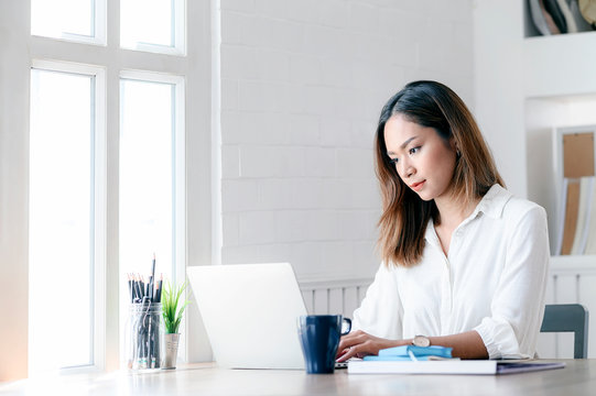Portrait of young businesswoman looking at laptop screen while sitting at office desk in modern office.