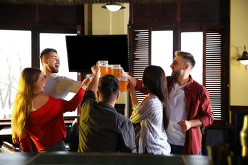 Group of friends celebrating victory of favorite football team in sport bar