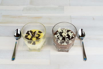 A glass with vanilla pudding and one with chocolate pudding