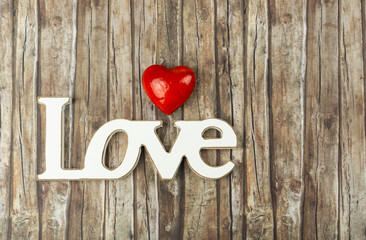 The word love in wooden letters with a white heart beside, wooden background