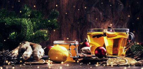 Foto op Plexiglas Thee Winter hot tea with fruit, lemon and spices in glass cup with steam in Christmas or New Year's table setting, rustic wooden background