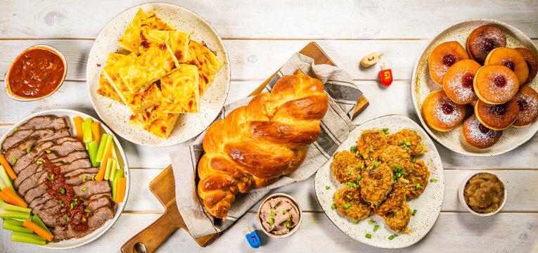 Selection of traditional hanukkah food for festive dinner - Potato Latkes, Applesauce, Challah, Beef Brisket, Sufganiot, Noodle Kugel, Julienned Vegetables