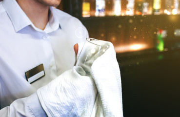 Old pub with bartender cleaning the glass with white towel on background. Empty name tag badge on the shirt uniform. Barman at his working place.