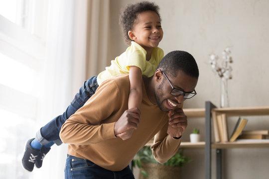 Smiling preschooler boy piggyback playing with dad