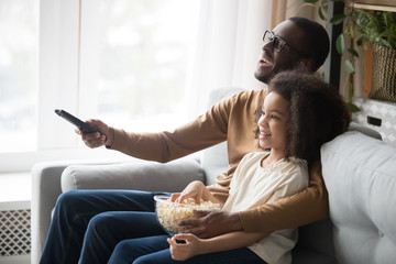 Happy black dad and daughter cuddle watching TV Wall mural