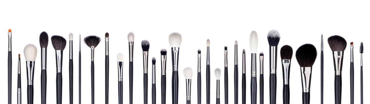 Set of make-up brushes lined up in alternating pattern. Isolated on white