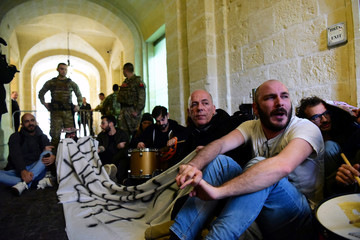 Activists sit after having barged into the building of Malta's Prime Minister Joseph Muscat's office, demanding his resignation in the wake of developments in case of the 2017 murder of anti-corruption journalist Daphne Caruana Galizia, in Valletta