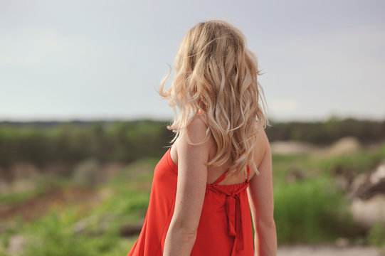 Rear view of blonde woman in red dress looking into the distance at nature. Travelling concept